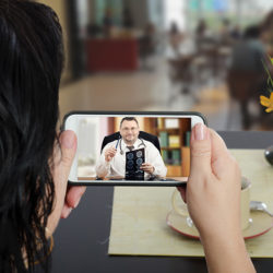 Woman sits at a cafe table and communicates with telemedicine doctor by cellphone. In touchscreen, male physician reviewing brain x-ray image. Patient has ability to reach telemedicine specialist remotely by mobile application. Horizontal indoors back side shot on cafe blurred background